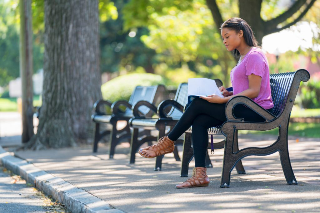 Student studying on campus bench